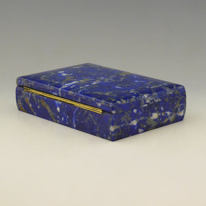A view from an angle with the back left corner in the foreground of a Lapis Lazuli box with a cobalt blue base colour and white, beige and dark blue mottling running through the stone and a gilt hinge along the rear edge. White background.