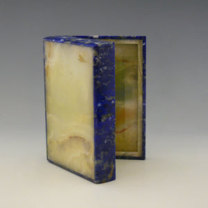 An open stone box resting on it's side with the lid open viewed from below. The base and inside are yellow stone. The outside of the box is Lapis Lazuli with a cobalt blue base colour and white, beige and dark blue mottling running through the stone. white background.