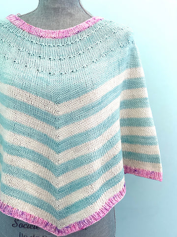 An aqua and white striped poncho, with pink neck and hem edges. The upper portion of the yoke (above the main striped section) is solid aqua.