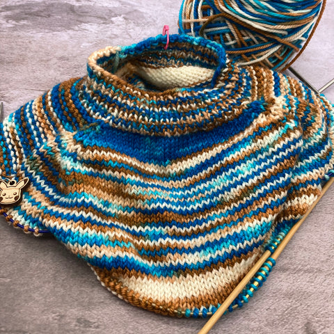 the neck and yoke of a top-down baby sweater knit with a variegated white, blue, and tan yarn. The partial ball of yarn is in the background, and the body of the sweater and the sleeves are on circular knitting needles