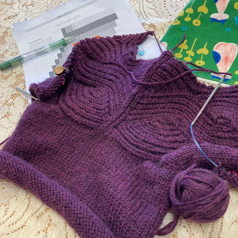 The top portion of a deep plum wool sweater with brioche wave lapels is on top of a cream lace tablecloth, along with a pattern page, a green mechanical pencil, and a green zippered project bag with stylized cats on it.