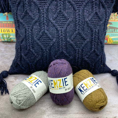 A pillow with a handknit cabled cover in very dark purple tweed is sitting on a grey surface. A colorful travel poster is visible in the background, and there are three skeins of HiKoo Kenzie yarn in front of it. On the left is a light grey, in the center is a medium purple, and on the right is a brassy green color.