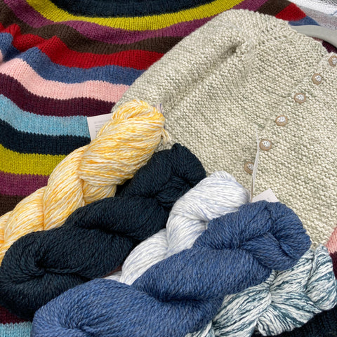 Three skeins of white cotton yarn speckled with yellow, pale blue, and teal, plus two skeins of wool yarn in dark blue and medium blue , arranged on top of a nine-color striped sweater and a baby cardigan knit with white and green speckled yarn