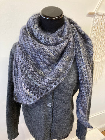 a plain grey cardigan on a dress form, with a large crochet shawl in black, grey, and gold mohair blend yarn