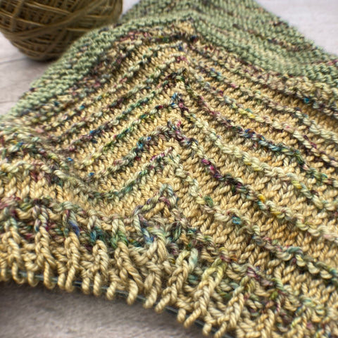 Close-up view of the beginning of a triangular knitted shawl. The section closest to the camera is twisted 1x1 ribbing, following that is a section of stockinette with garter ridges, and behind that is a section of garter stitch stripes. The colors are green, gold, and multicolored speckles.