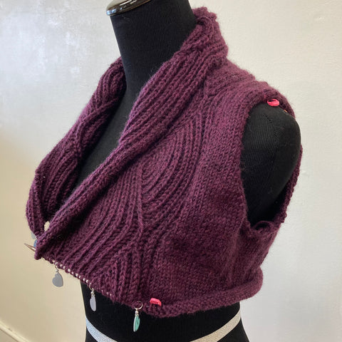 Partially complete deep plum sweater displayed on a black fabric mannequin. Lapels are brioche waves, and the project is complete to three or four inches below the bottom of the armhole.