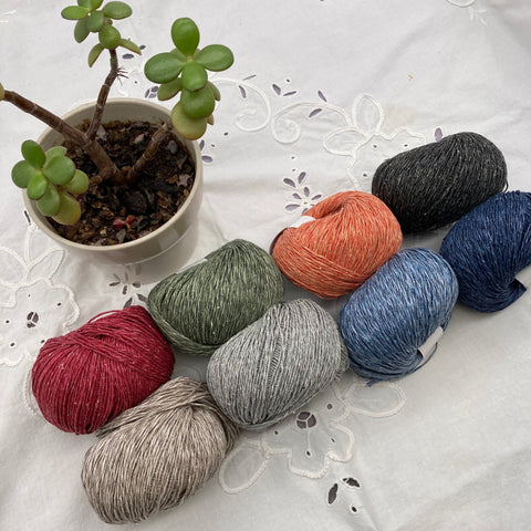 Eight balls of linen and silk yarn are arranged in two parallel lines diagonally across the frame. The colors of the top row are red, green, pale orange, and charcoal. The bottom row is tan, light grey, light blue, and dark blue. They are resting on a white cutwork tablecloth, and a jade plant is in the upper left corner.