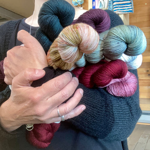 A woman wearing a black cardigan is hugging seven skeins of yarn: deep teal, a dark rosy plum, a pastel variegated color, a lightly speckled greyish green, a deep crimson, and a deep rose. The seventh skein is barely visible.