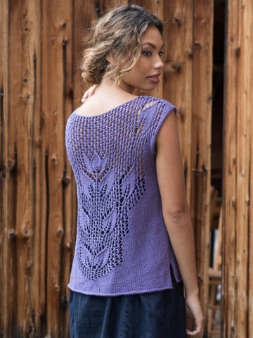 Model is wearing lavender tee, and is facing a wood wall to display the lacy back panel of the sweater.