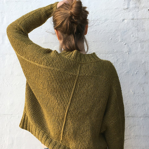 view from the back of a woman wearing a gold garter stitch sweater with exposed joinery details