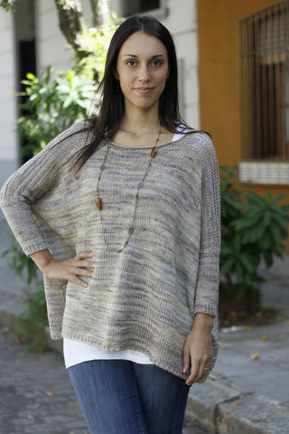 Designer Joji Locatelli wearing a boxy sweater knit from light tonal grey yarn. She is posed with one hand on her right hip. There is a building in the background, along with some plants.