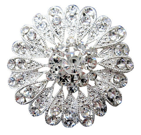 Intricate brooch with clear crystals on a silver tone finish, brooch measures 5cm by 5cm.