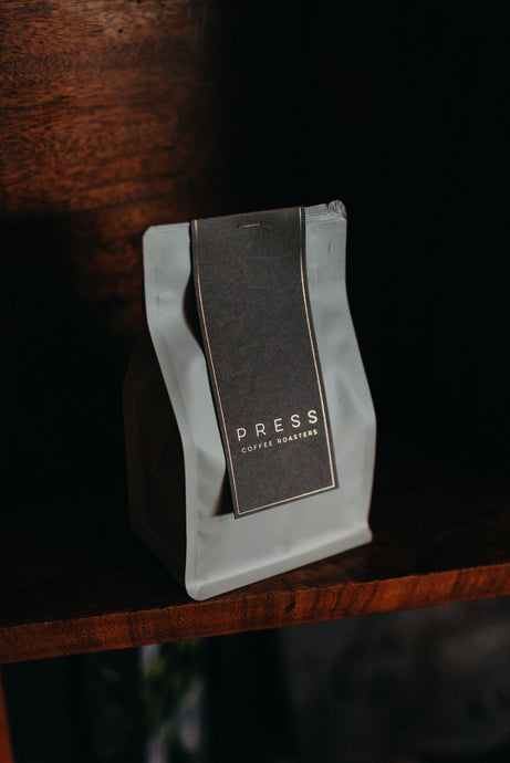 Bag of coffee beans from Press cafe in Dubbo NSW. White bag, grey label with copper logo.