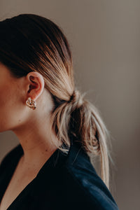 Side profile of female model wearing gold earring and hair tied loosely back.