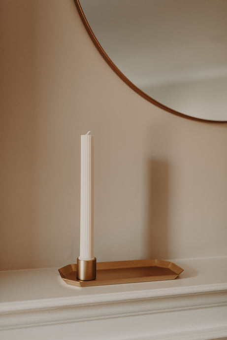 Off white pillar candle in a brass holder and on a brass tray on mantle piece. All sold at unparalleled.studio