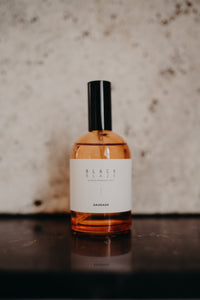 Saudade interior fragrance spray bottle. by unparalleled.studio on black marble base.
