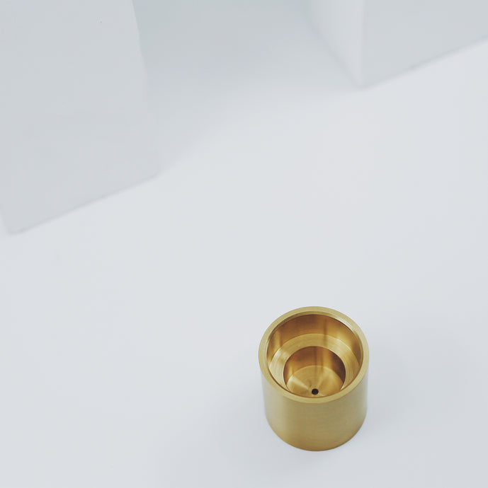 Solid brass incense and candle holder by black blaze. White background.