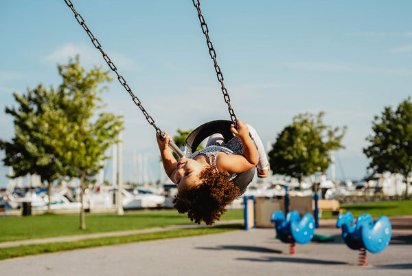Boy on swing with curly hair