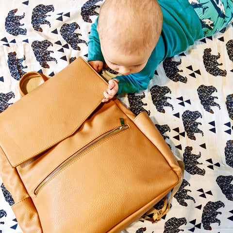 Tan changing bag with baby lying next to it