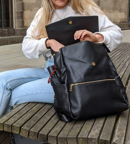 Black changing backpack being opened by model