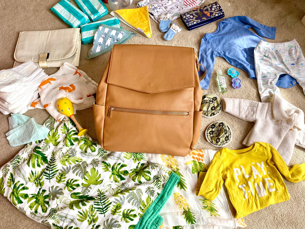 Tan backpack changing bag with baby items laid out on the floor