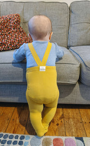 Baby wearing mustard baby tights with braces standing next to sofa