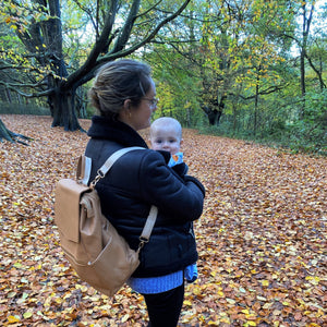 Woman wearing tan backpack changing bag in forest