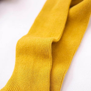 Close-up of mustard baby tights with braces showing knitted fabric