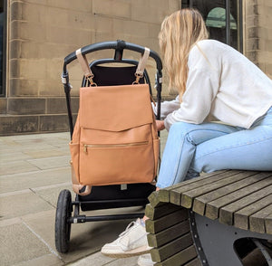 Tan backpack changing bag strapped to pram handlebar