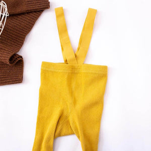 Mustard baby tights with braces on floor in flatlay style