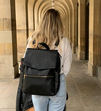 Load image into Gallery viewer, Lifestyle shot of model wearing black backpack changing bag