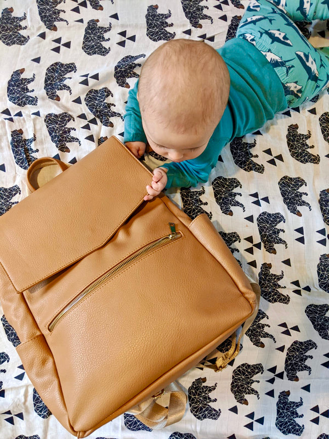 Baby lying on tummy next to tan backpack changing bag