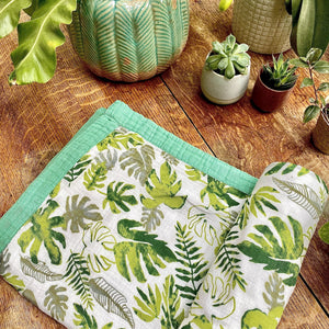 Bamboo baby blanket with tropical leaf print on wooden table with plants