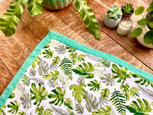 Load image into Gallery viewer, Bamboo baby blanket with tropical leaf print on wooden table showing blanket edge