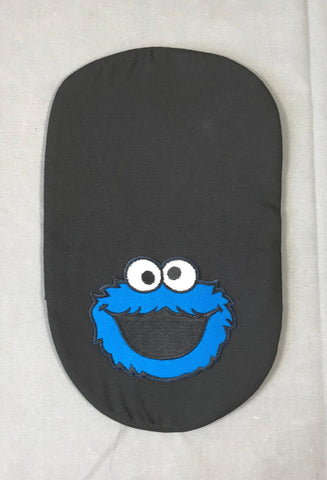 An image of a black ostomy bag cover with an embroidered Cookie Monster patch
