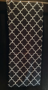 A black and white geometric patterned scarf, hanging on a gold hanger