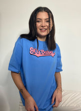 Load image into Gallery viewer, A woman with dark hair, two braids at the front, wearing a light blue, long t-shirt with the words '90s baby' in pink