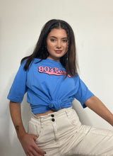 Load image into Gallery viewer, A woman with dark hair, two braids at the front, wearing a blue t-shirt, knotted at the bottom, and white trousers. The t-shirt has '90s baby' in pink across the front.