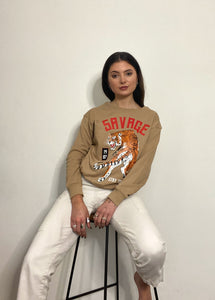 A woman with dark brown hair leaning back on a bar stool, wearing white trousers and a beige top with a tiger print below a print of the word 'savage' in red letters