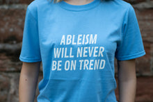 "Load image into Gallery viewer, A close up image of the front of a light blue t-shirt, which has the words ""ableism will never be on trend"" in white"