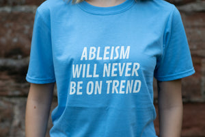"A close up image of the front of a light blue t-shirt, which has the words ""ableism will never be on trend"" in white"