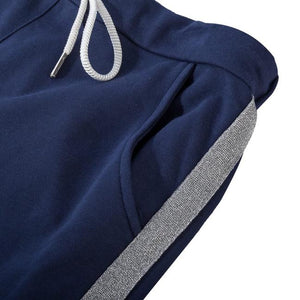 A close up of one of the pockets on the navy joggers. The silver stripe which runs down the side of the joggers is also visible.