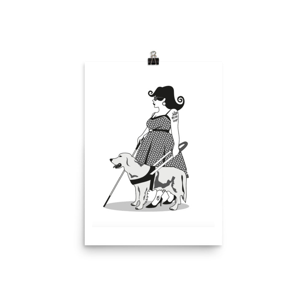 A white poster, held up by a black bulldog clip, with a black and white print in the centre depicting a curvy women with flicked out dark hair. She is wearing a polkadot fifties dress and has a cane and a guide dog