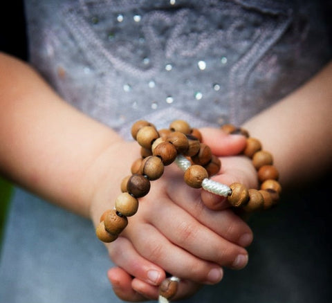 Sandalwood meditation bracelet being held in hand