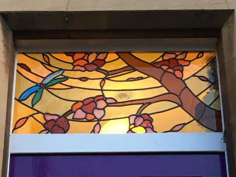 Whimsical maximalist floral stained glass panel with a dragonfly above a door in a victorian home