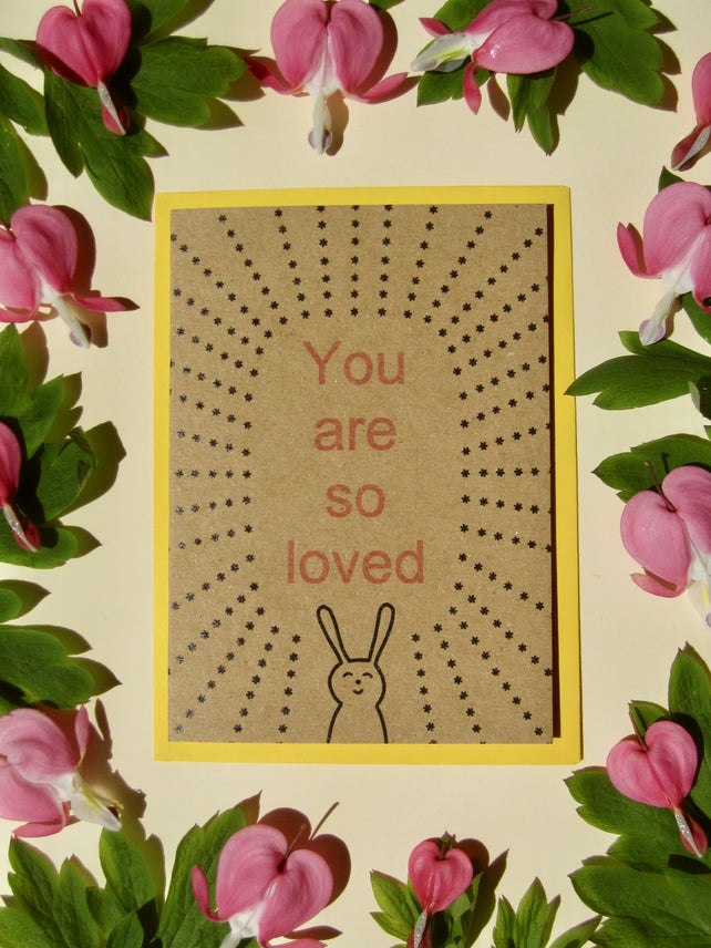 Glass Designs Ransom Designs You are so loved card. Brown recycled paper with black line drawing illustration of smily bunny with little black stars