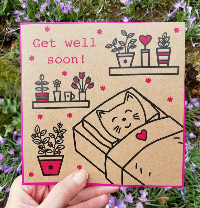 Glass Designs Ransom Designs  Get well soon card with a cat tucked up in bed and pink and black plants on shelves. Illustration line drawing card.