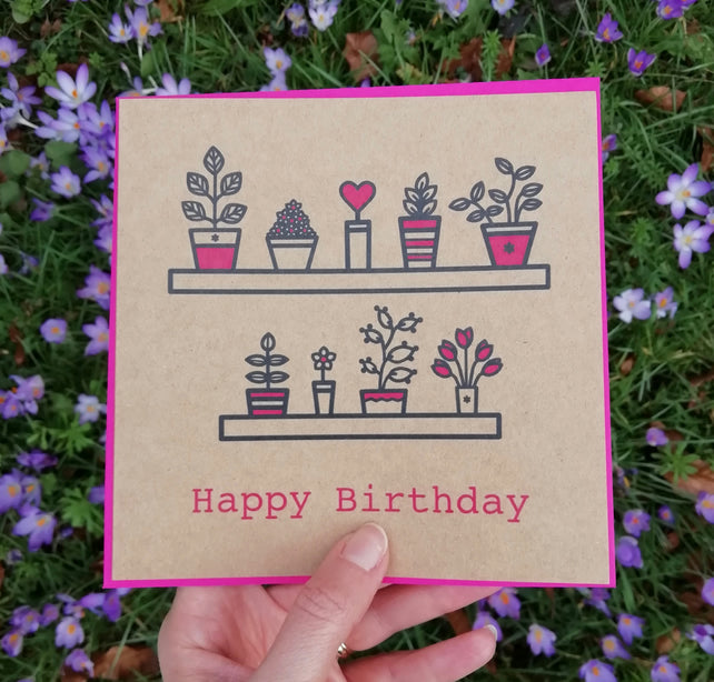 Glass Designs Ransom Designs Botanical Birthday card with black and pink plants on shelves and pink happy birthday writings. On brown recycled paper