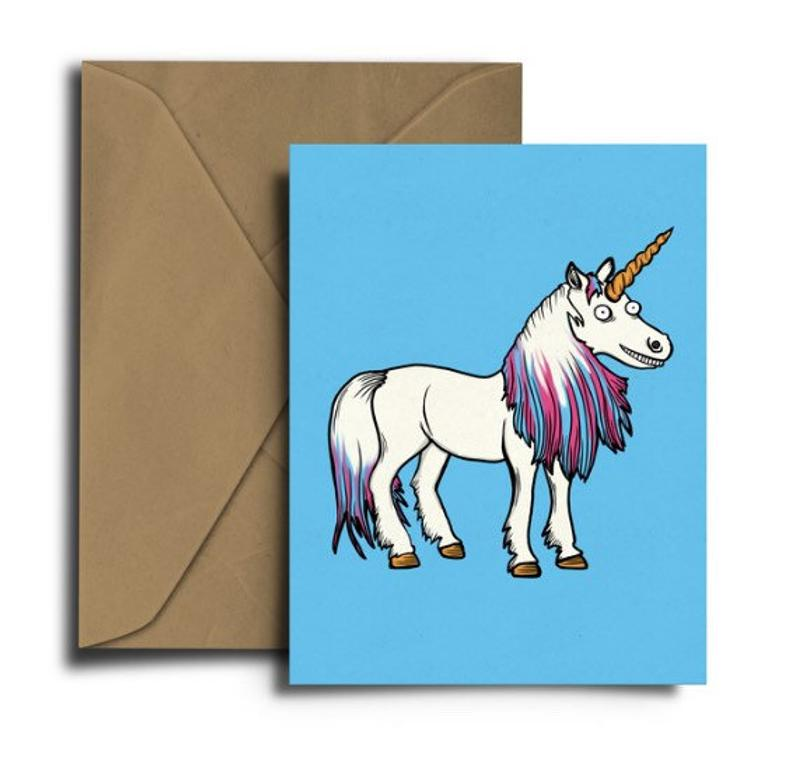 Glass Designs Dixon Does Doodles card with a smiley unicorn on a blue background