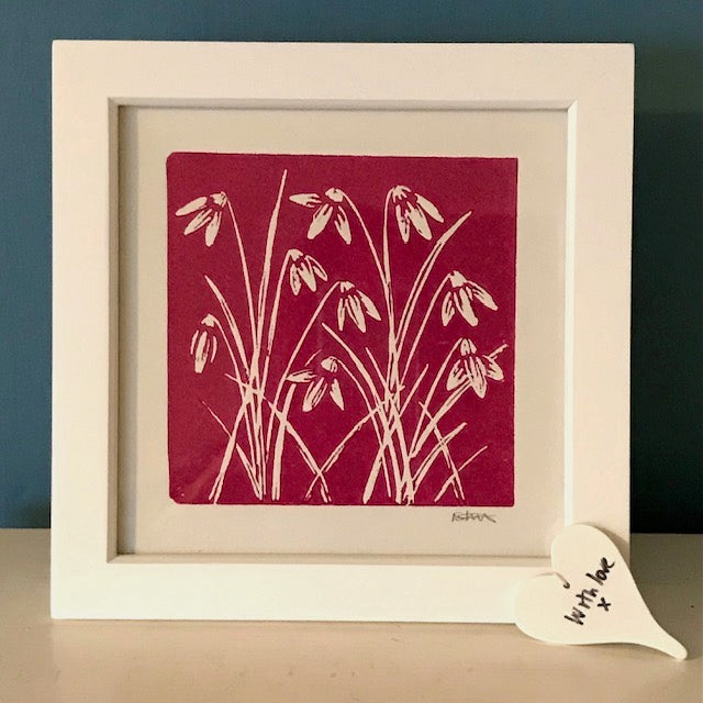 Pink background with snowdrops lino print in a white frame.